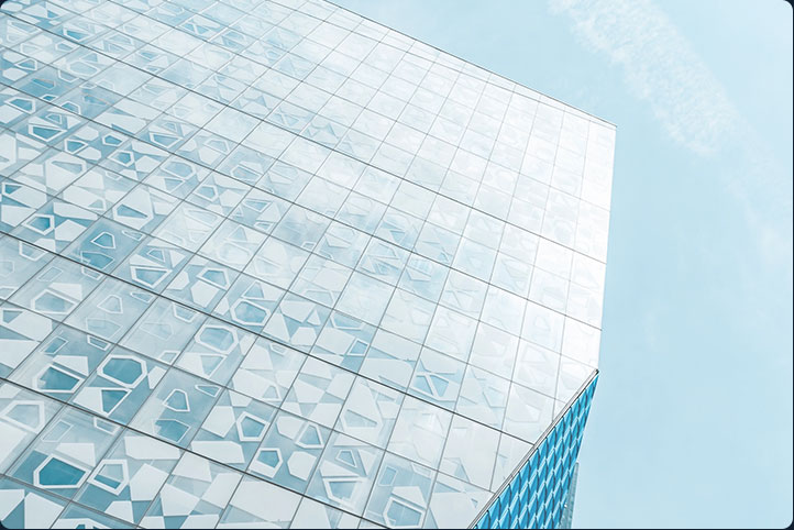 Picture of a shining glass building looking up to blue sky for Cloud Solutions by CyberNorth.
